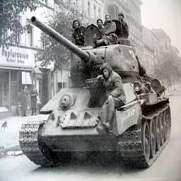 Танк Т-34 стоит напротив бумажно-канцелярского магазина на улице Берлина.